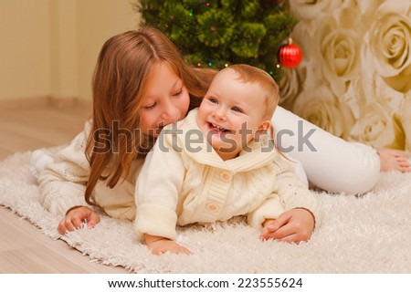 Older and one younger sister lay on the carpet, playing, laughing, against the background of the Christmas tree. - stock photo