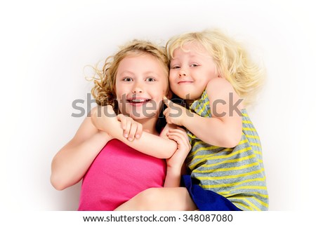 Older and younger sisters hugging each other and laughing. Happy childhood. Family concept. Isolated over white. - stock photo