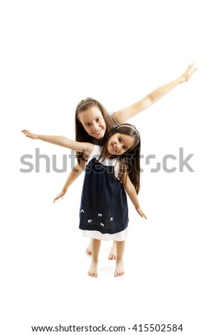 Older and younger sisters playing together and laughing. Happy childhood. Family concept. Isolated on white background  - stock photo