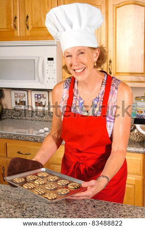 older attractive woman in red apron and white chefs hat holding a tray of cookies and tasting them - stock photo