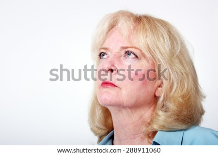 Older blond haired woman looking upward with a solemn expression.  Model is isolated on a white background and there is ample copy space. - stock photo