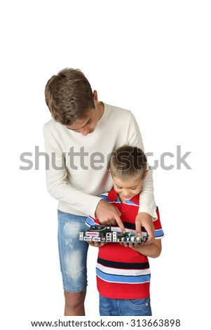 Older boy helps his little brother to explore computer cir?uit board isolated on white background - stock photo