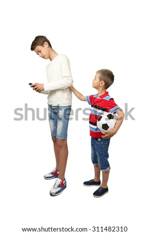 Older boy looks at his smartphone when little brother asks him to play soccer isolated on white background - internet and technology against sport and physical activity