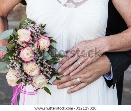 older bride and groom hands and rings with flowers - stock photo