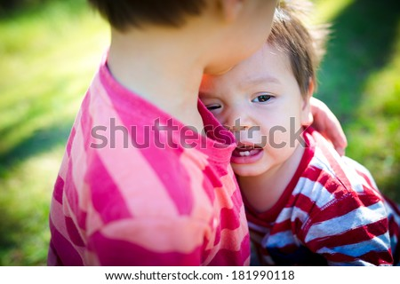 Older brother comforts his crying baby brother outdoor in the park - stock photo