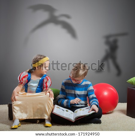 Older brother reading a fairy tale about a knight and a dragon to his little sister  - stock photo