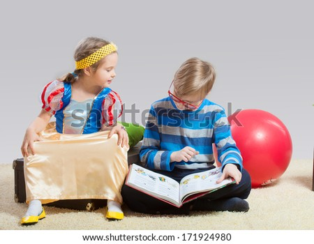 Older brother reading a fairy tale to his little sister - stock photo