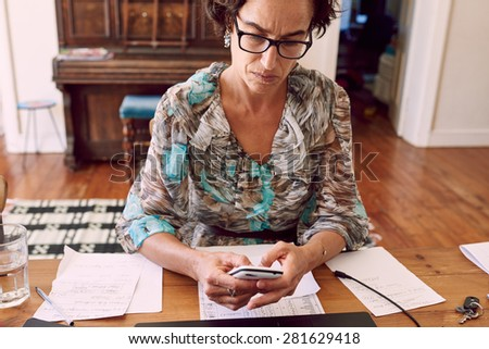 older business woman busy reading a text message on her cell phone while wearing glasses and sitting at her wooden desk - stock photo