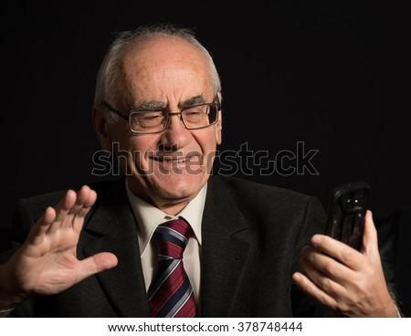 older businessman, wearing eyeglasses on black background, uses smart phone, has video chat - stock photo