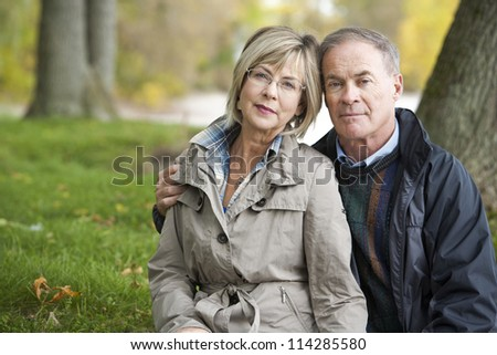 older casual couple sitting in the grass outdoors - stock photo