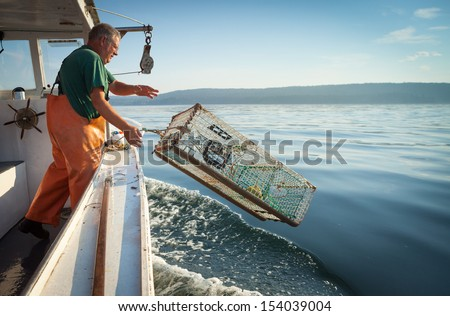 older, caucasian Man in overalls standing on boat throwing lobster trap into water, Maine, USA - stock photo