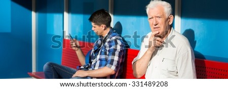 Older confused man and young boy on a bus stop - stock photo