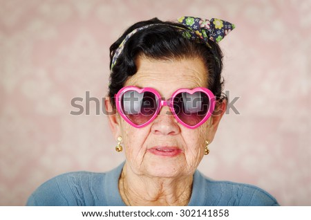Older cool hispanic woman wearing blue sweater, flower pattern bow on head and pink heartshaped sunglasses looking into camera. - stock photo