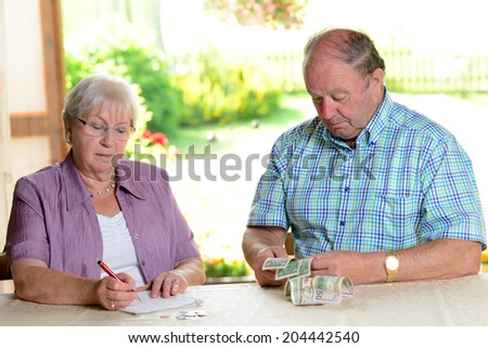 older couple calculating her little budget - stock photo