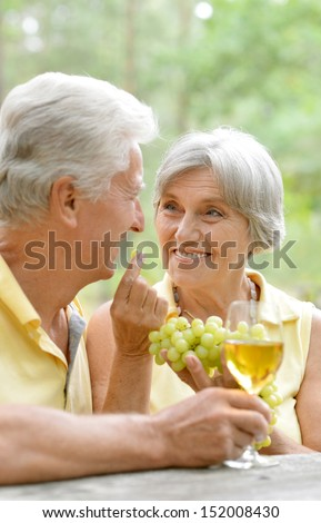 older couple drinking wine. Wife treats her husband grapes