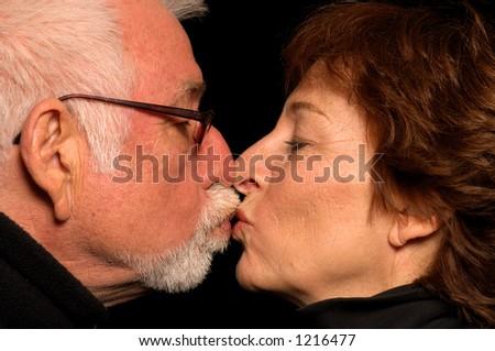 Older couple in love kisses - stock photo