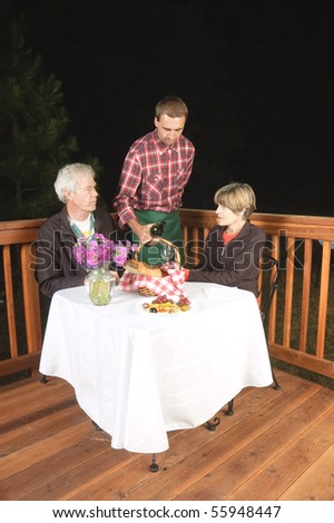 older couple in outdoor restaurant at night - waiter has served the wine to the man, to see if it is acceptable, from the look on his face it meets his requirements and is satisfactory:) - stock photo