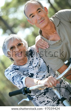 Older couple riding bikes in the countryside - stock photo