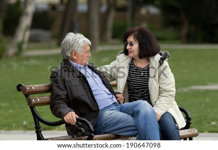 Older couple sitting and talking on bench in park - stock photo