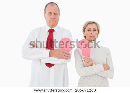 Older couple standing holding broken pink heart on white background - stock photo
