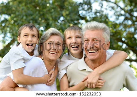 Older couple standing with their grandchildren in summer park