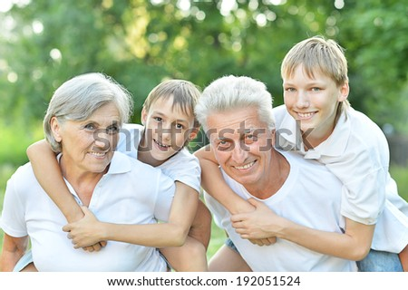 Older couple standing with their grandchildren in summer park - stock photo
