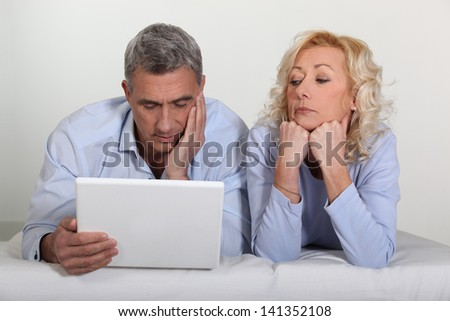 Older couple with a laptop - stock photo