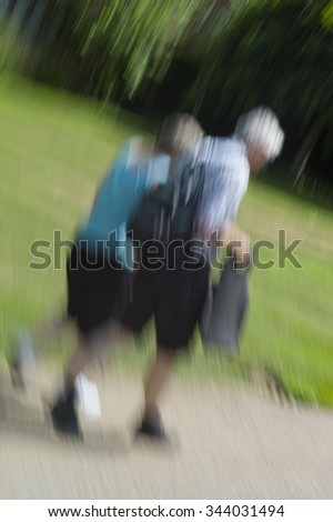 Older couple with bare legs walk in a park on a sunny day, photographed with a rotating camera - stock photo