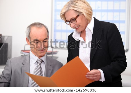 Older couple working in an office - stock photo