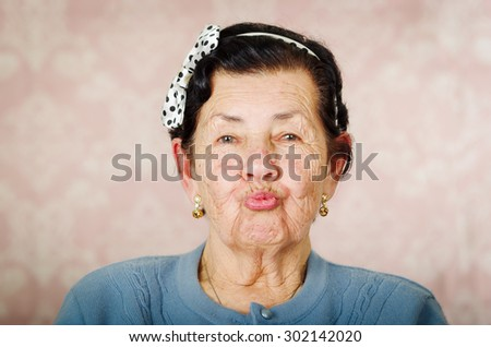 Older cute hispanic woman wearing blue sweater and polka dot bowtie on head making kiss lips for the camera. - stock photo
