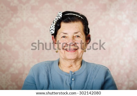 Older cute hispanic woman wearing blue sweater and polka dot bowtie on head smiling happily in front of pink wallpaper. - stock photo