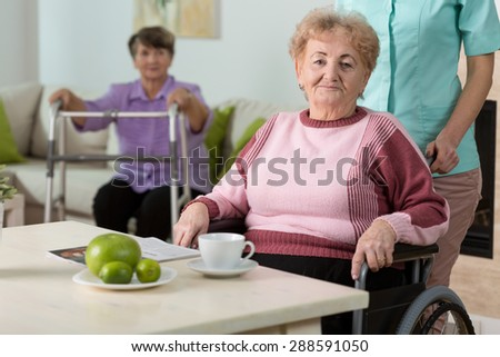 Older disabled woman on wheelchair in nursing home - stock photo