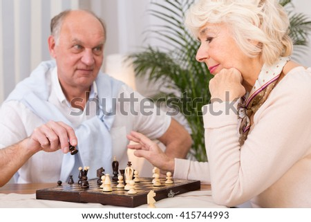 Older elegant woman playing chess with her smart elderly husband at home
