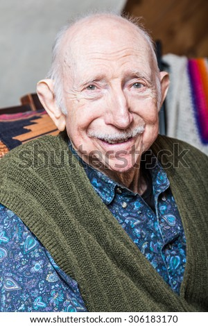 Older gentleman in green vest smiling into the camera - stock photo
