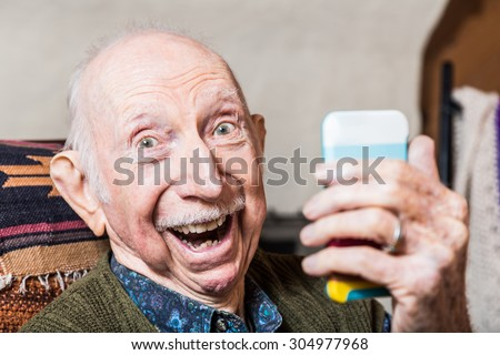 Older gentleman taking a selfie with smartphone - stock photo