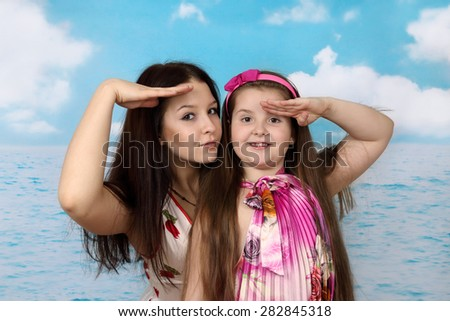 Older girl and her younger sister on sea background looking into the distance - summer, sea, vacation, travel concept - stock photo