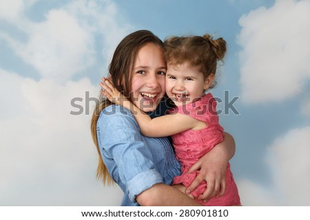 Older girl carries little sister on hands on cloudy blue sky background - Family, childcare and love concept - stock photo