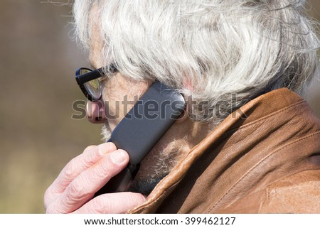 Older Grey Haired Man Calling on a Flip Phone