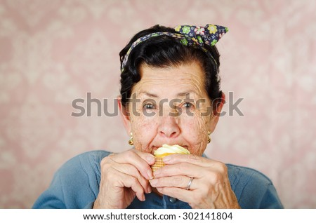 Older hispanic happy woman wearing blue sweater and flower pattern bow on head sitting in front of camera having a bite off cupcake. - stock photo