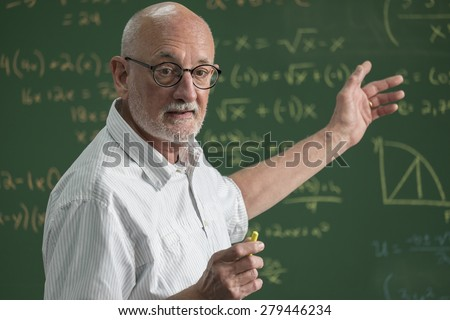 Older male teacher standing in front of a chalkboard in a classroom - stock photo