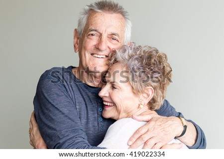 Older man and woman hugging each other and smiling - stock photo