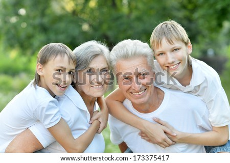 Older man and woman with their grandchildren having fun outdoors