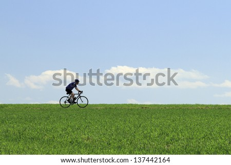 Older man cycling trough the fields