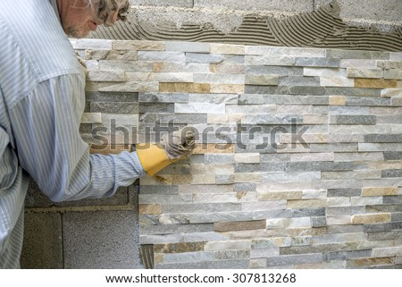 Older man decorating a wall with ornamental tiles pressing and fixating  a tile firmly into a glue with his fist. - stock photo