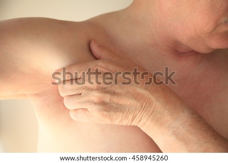 Older man has a hand next to his armpit area. - stock photo