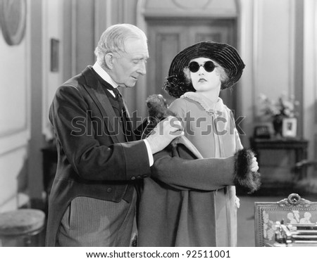 Older man helping a young woman into her coat - stock photo
