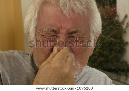 Older man holding nose sneezing. - stock photo
