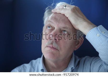 older man is indecisive and perplexed - stock photo