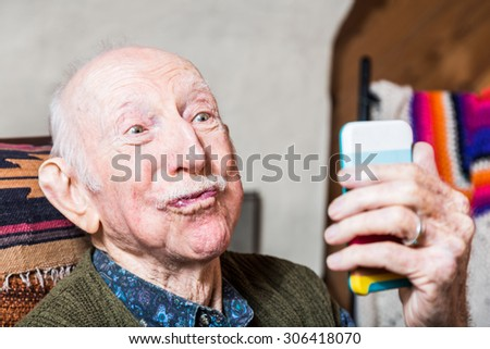 Older man looking at camera while taking silly face selfie - stock photo