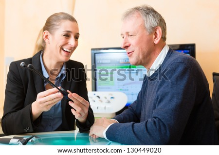 Older man or pensioner with a hearing problem make a hearing test and may need a hearing aid - stock photo